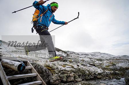 Hiker jumping across mountain stream, Norway, Europe