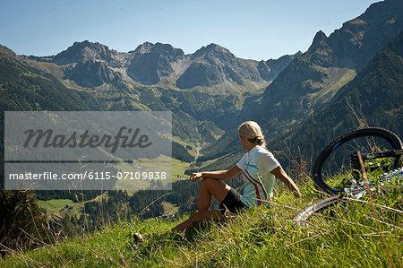 Female cyclist takes a rest looking at mountains, Kleinwalsertal, Vorarlberg, Austria