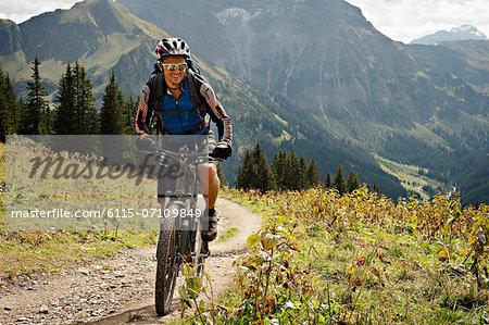 Man mountain biking along a track trail, Kleinwalsertal, Vorarlberg, Austria