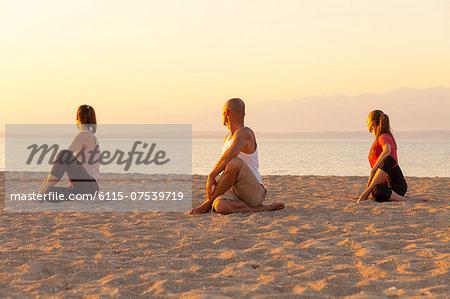 People practising yoga on beach, rear view