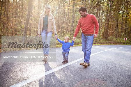 Family with one child walking across street, Osijek, Croatia
