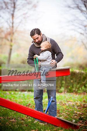 Father with son playing on a swing, Osijek, Croatia