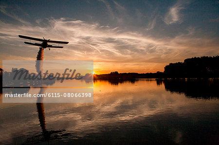 Biplane flying over Drava river at sunset, Osijek, Croatia