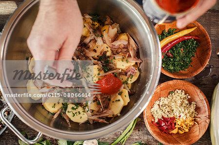 Person preparing potato salad