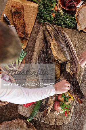 Person preparing pike on cutting board