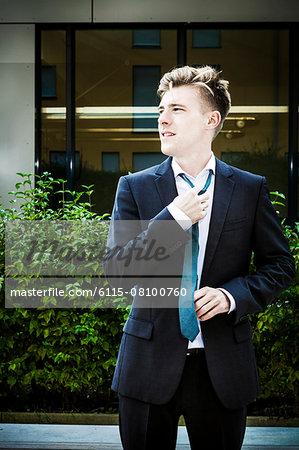 Young businessman adjusting his tie, Munich, Bavaria, Germany