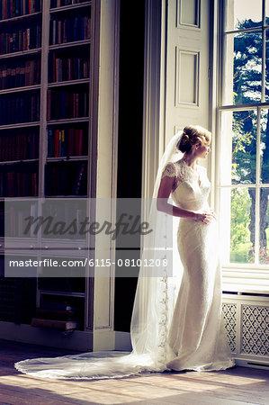 Wedding preparations, Bride in wedding dress by window, Dorset, England