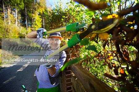 Senior man trimming plants by garden fence, Munich, Bavaria, Germany