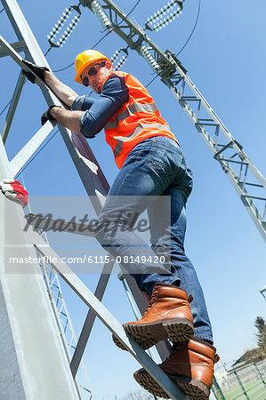 Engineer climbing electricity pylon