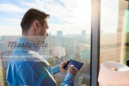 Businessman in apartment using digital tablet