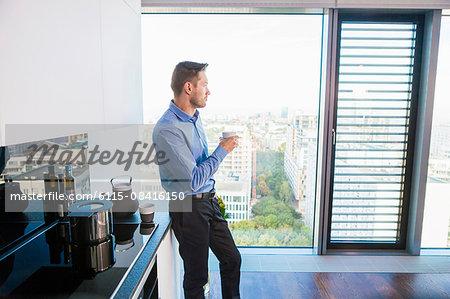 Businessman in apartment having a coffee break
