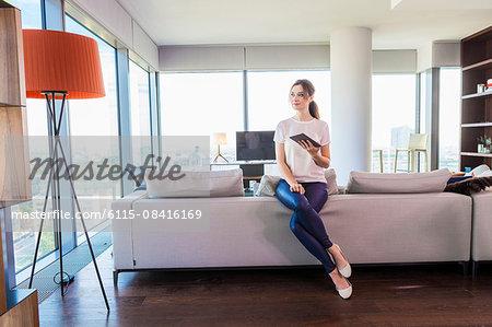 Woman in apartment using digital tablet