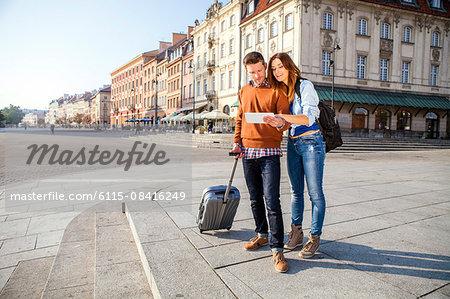 Mid adult couple on a city break using digital tablet