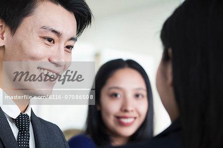 Co-workers talking in office