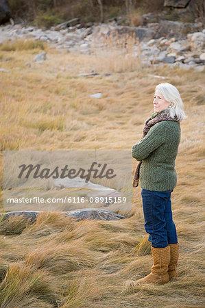 Senior woman standing on long grass