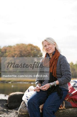 Senior woman sitting on rocks