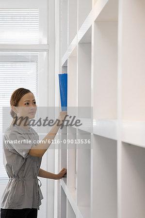 Woman by bookshelf