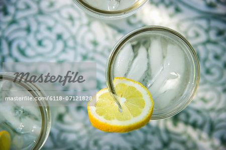 Making Lemonade. Overhead Shot Of Lemonade Glasses With A Fresh Slice Of Lemon In The Edge Of The Glass. Organic Lemonade Drinks.