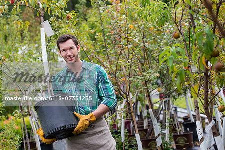 An organic flower plant nursery. A man working, carrying a sapling tree in a pot.