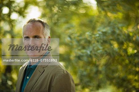 A mature man wearing a green shirt, in woodland.