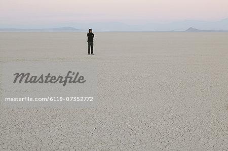 Man standing in vast, desert landscape