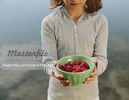 Nine year old girl holding bowl of organic raspberries
