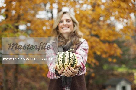Organic farm. A woman holding a large striped squash vegetable.