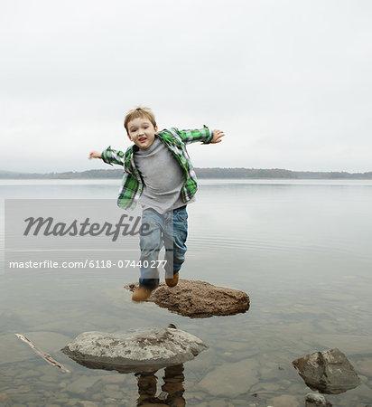 A day out at Ashokan lake. A boy jumping across stepping stones.