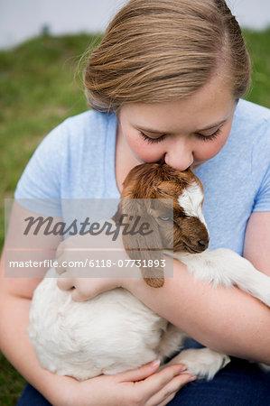 A girl cuddling a baby goat.