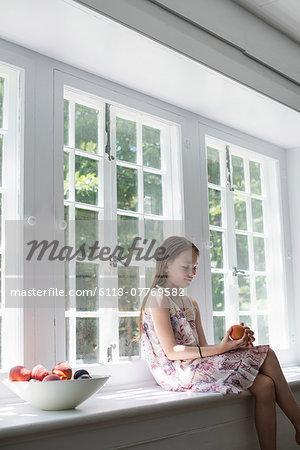 Girl sitting by a window.