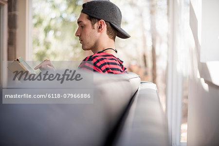 Man wearing a baseball cap backwards, sitting on a sofa, looking at a digital tablet.