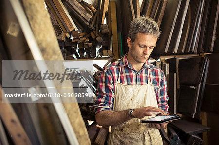 An antique furniture restorer in his workshop, using a digital tablet.