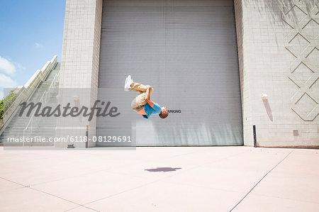 Young man somersaulting in front of a garage door.