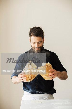 Baker holding two freshly baked loaves of bread.