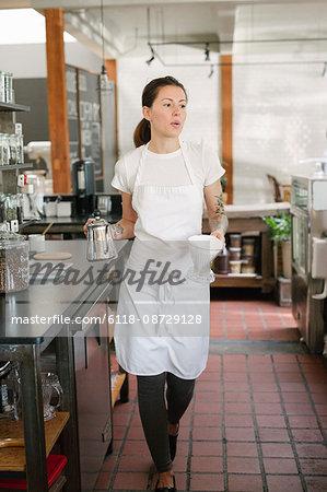 Woman wearing an apron walking along a corridor, carrying a coffee pot and filter.