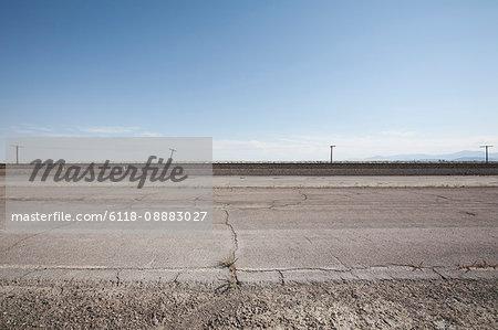 Pylons rising above a concrete surface against a blue sky.
