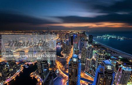 Cityscape of the Dubai, United Arab Emirates at dusk, with illuminated skyscrapers and coastline of the Persian Gulf.