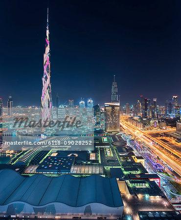 Cityscape of Dubai, United Arab Emirates at dusk, with illuminated Burj Khalifa skyscraper in the foreground.