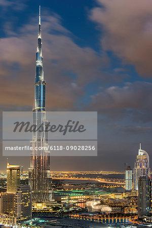 Cityscape of Dubai, United Arab Emirates, with illuminated Burj Khalifa skyscraper in the foreground.