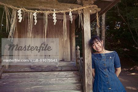 Young woman wearing blue dress standing under shimenawa ropes at Shinto Sakurai Shrine, Fukuoka, Japan, smiling at camera.