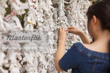 Young woman wearing blue dress tying omikuji fortune telling paper at Shinto Sakurai Shrine, Fukuoka, Japan.