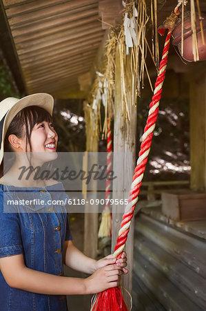 Young woman wearing blue dress and hat pulling on red rope at Shinto Sakurai Shrine, Fukuoka, Japan.