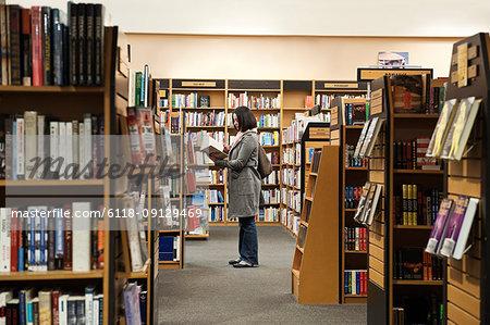Caucasian female browsing through books in a bookstore.