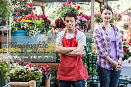 Caucasian man and woman employees of a garden centre nursery.