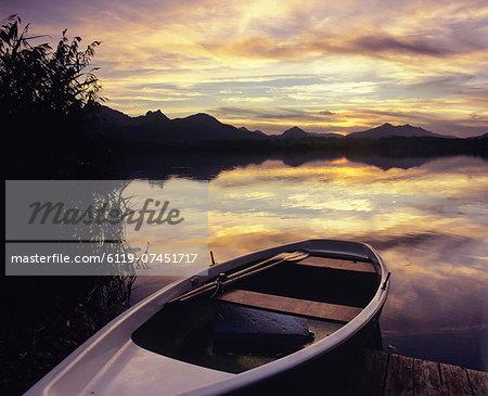 Rowing boat on Hopfensee Lake at sunset, near Fussen, Allgau, Bavaria, Germany, Europe