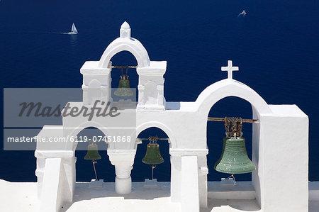 White bell tower and sailing boat, Oia, Santorini, Cyclades, Aegean Sea, Greek Islands, Greece, Europe