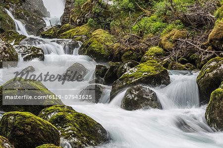 Slow shutter speed silky water of the Olden River as it flows along Briksdalen, Olden, Nordfjord, Norway, Scandinavia, Europe