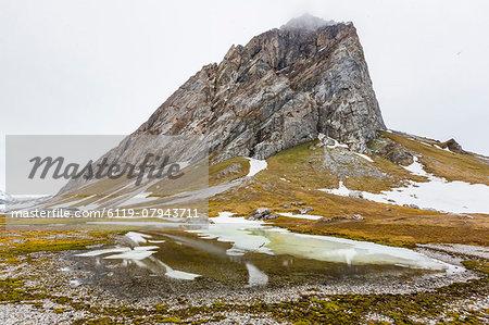 Gnalloden reflected in meltwater pond at Hornsund, Spitsbergen, Svalbard, Arctic, Norway, Scandinavia, Europe