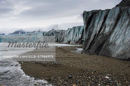 Gravel beach in front of a huge glacier in Hornsund, Svalbard, Arctic, Norway, Scandinavia, Europe