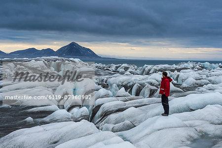 Man standing on a huge glacier in Hornsund, Svalbard, Arctic, Norway, Scandinavia, Europe